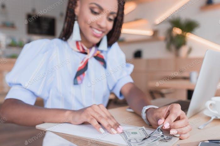 Joven afroamericana pagando con dinero en efectivo en la cafetería