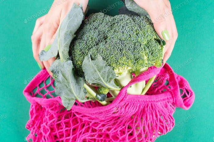 Woman holding pink reusable bag with broccoli
