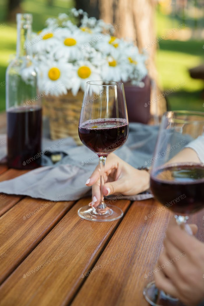 Cropped picture of women sitting outdoors in park drinking wine