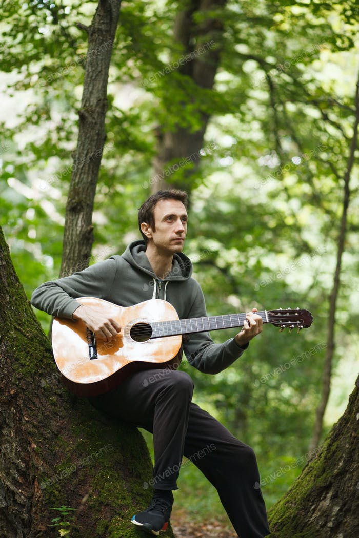 male guitarist playing acoustic guitar in green forest