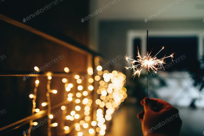 Sparklers on blurred christmas lights. Festive mood