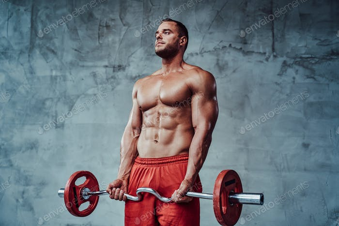 Powerful sportsman with formed body trains weightlifting