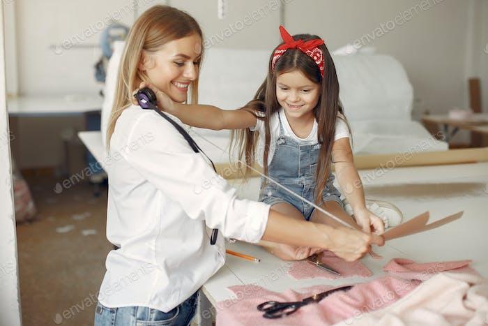 Mutter mit kleiner Tochter messen Sie den Stoff zum Nähen