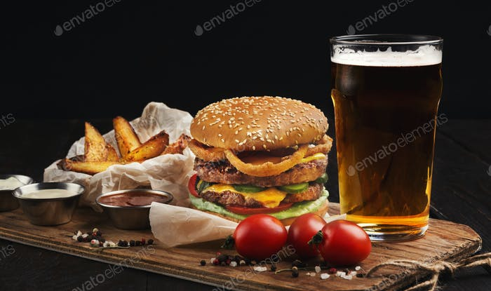 Hamburger made of beef and beer on wooden cutting board