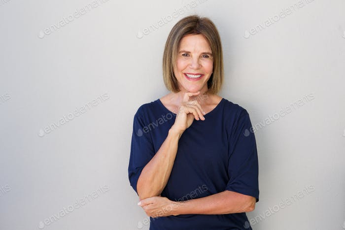 older woman smiling with hand to chin