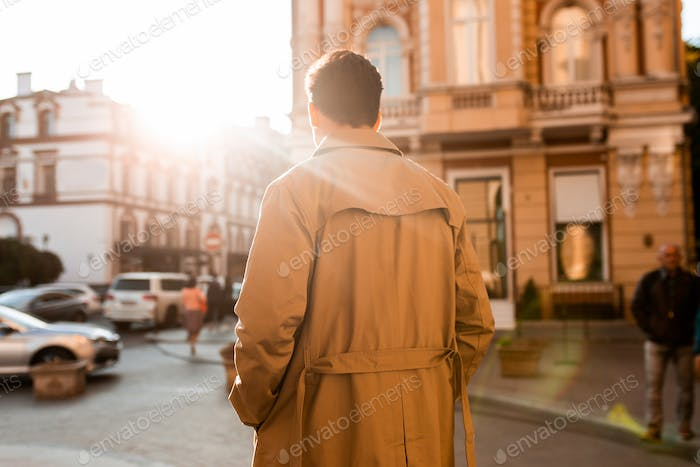 Back view of young confident man in trench coat walking through city street