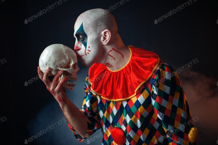 Mad bloody clown holds human skull, horror