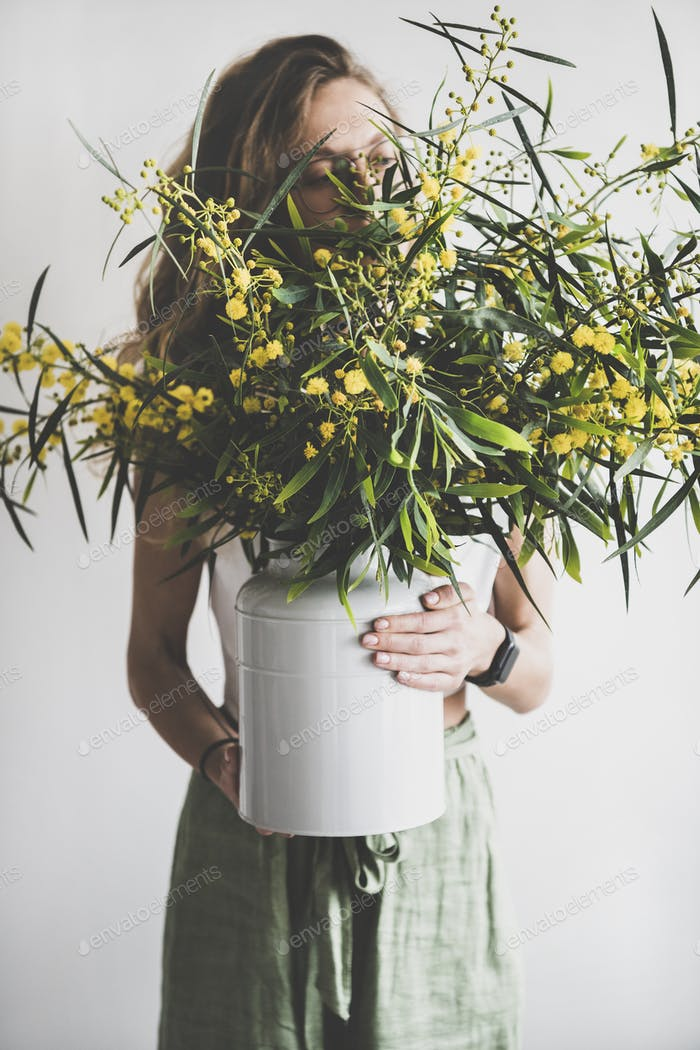 Spring mimosa branches in vase in hand of woman
