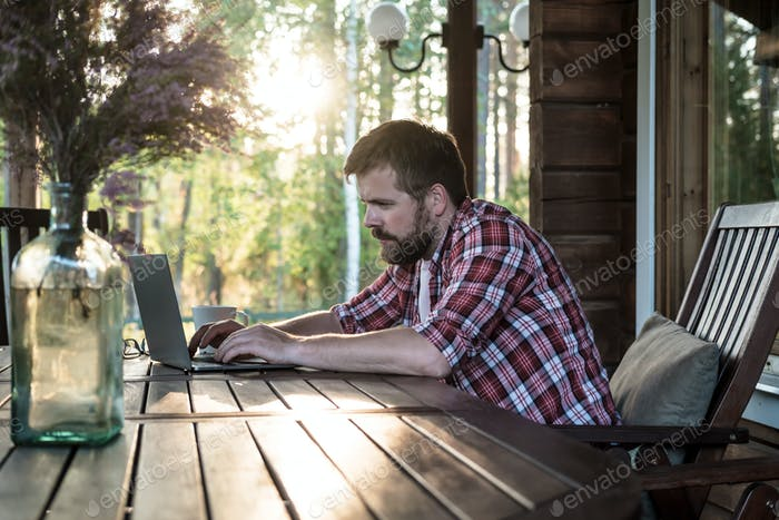 Bearded man works with a laptop on the outdoor terrace in his yard