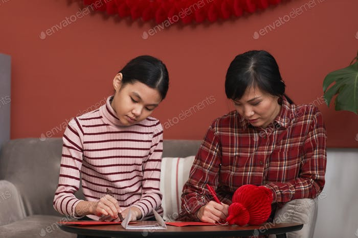 Mother And Daughter Preparing Red Envelopes