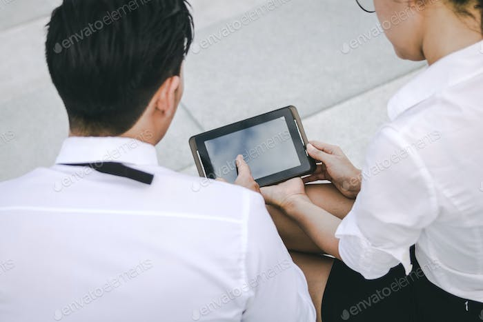 Two business people holding digital tablet and pointing on blank screen with serious expression.