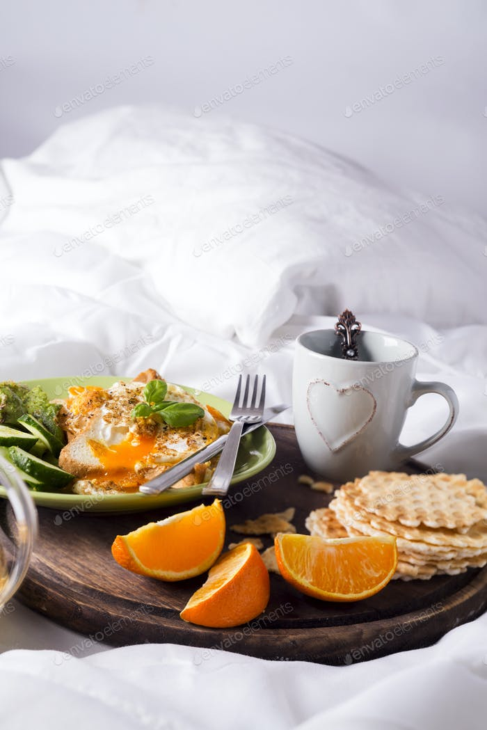 Fried eggs with toasts and tea in bed