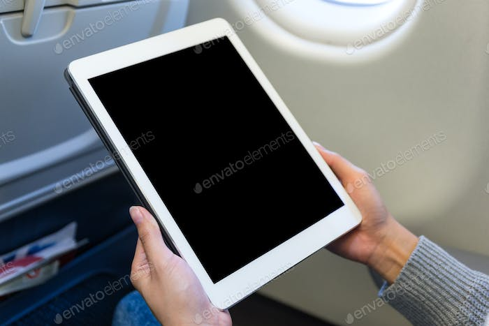 Woman use of the tablet in air plane