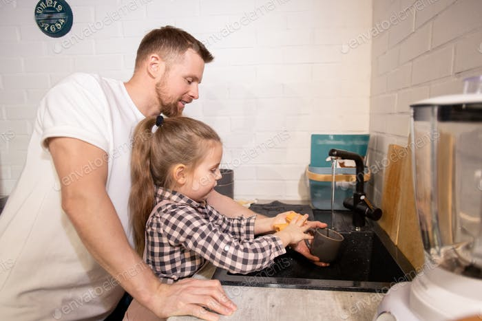 Cute little girl washing her mug over sink with duster and dish washer