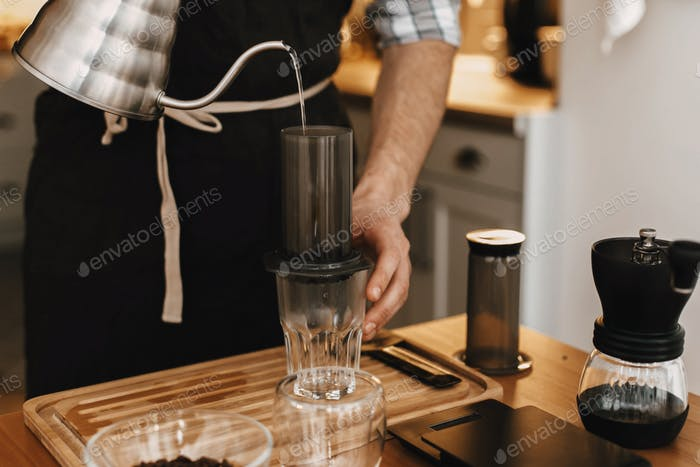 Hands holding steel kettle and aeropress, glass cup, scales, grinder on wooden table