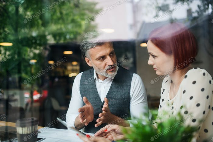 Man and woman having business meeting in a cafe, using tablet
