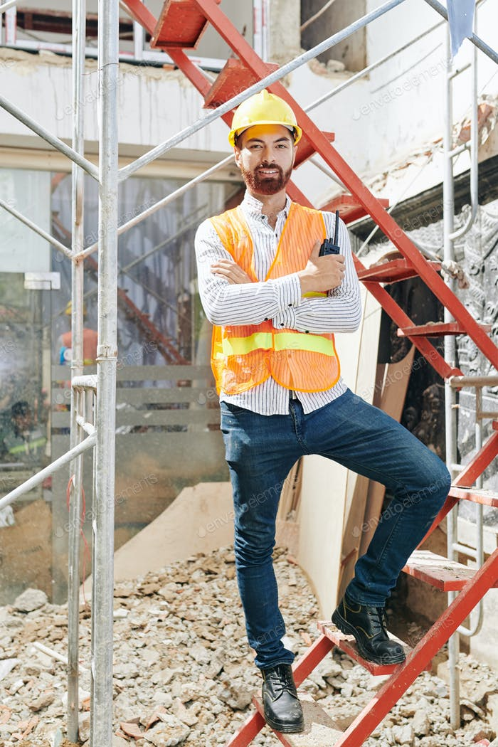 Confident contractor standing on ladder