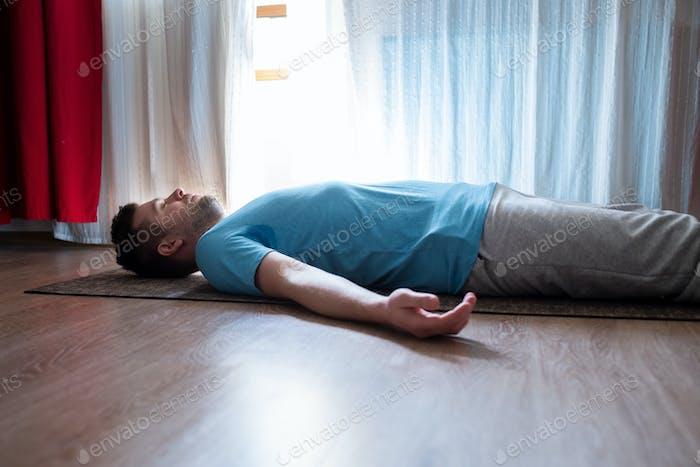 Junger Mann meditiert auf einem Boden und liegend in Shavasana Pose in seinem Wohnzimmer.