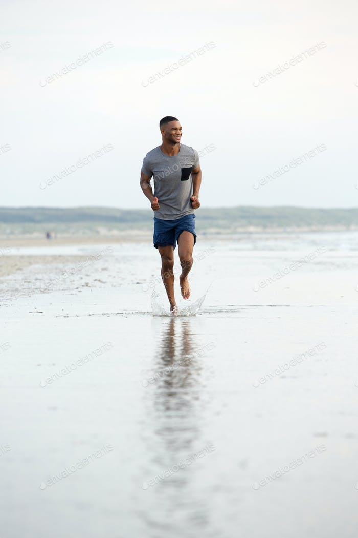 Man running barefoot on beach by water