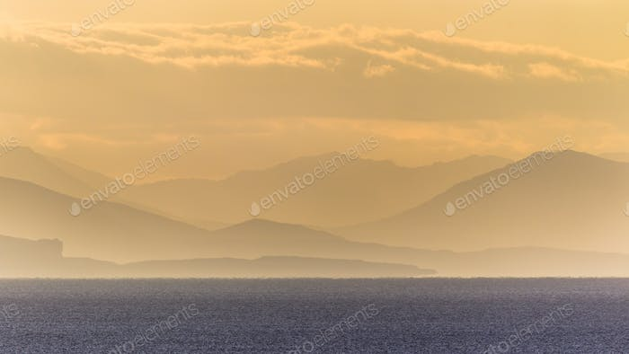 Silhouettes of hills over ocean