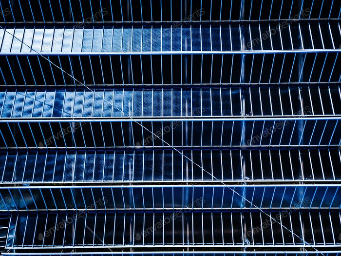 Aerial view of farming glasshouses or greenhouses close-up. Blue glass abstract background