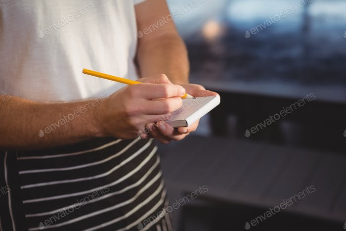 Mid section of waiter taking order