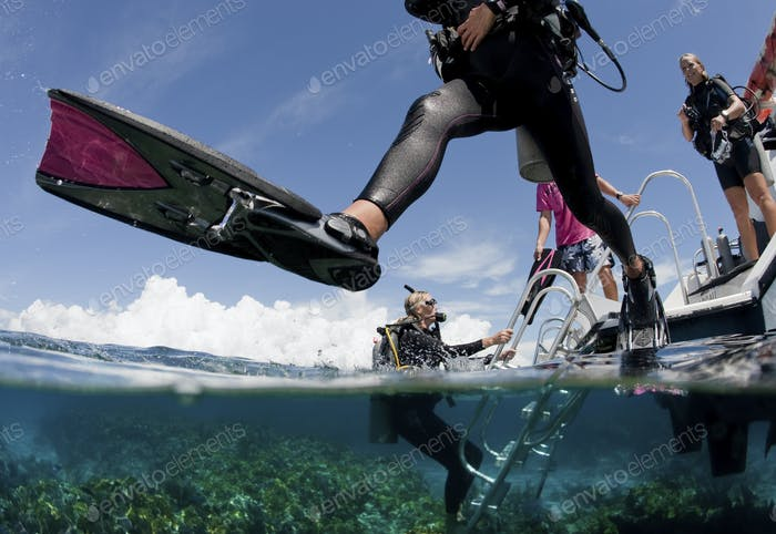 Scuba diver enters water from boat via giant stride entry.,Off to an adventure.