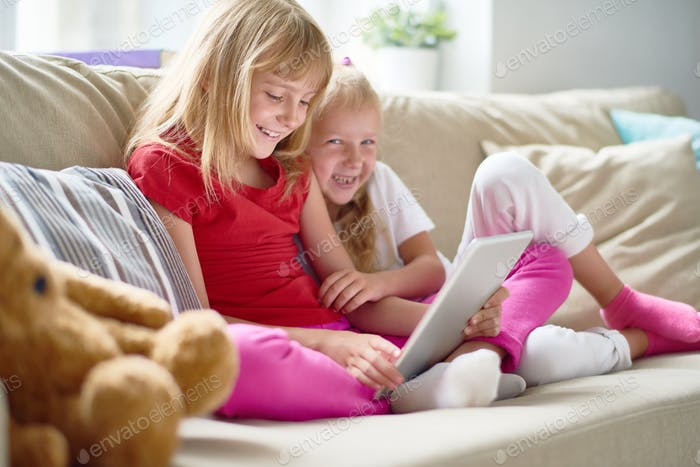 Cheerful Little Sisters at Living Room