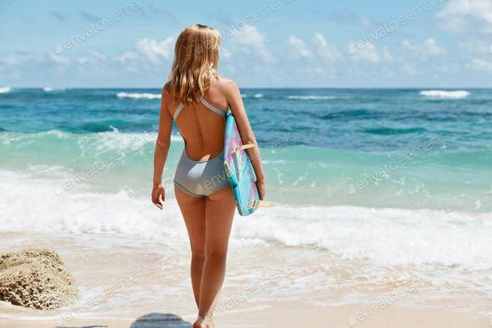 Full length portrait of slim female with light hair, wears blue swimsuit, stands against ocean beaut