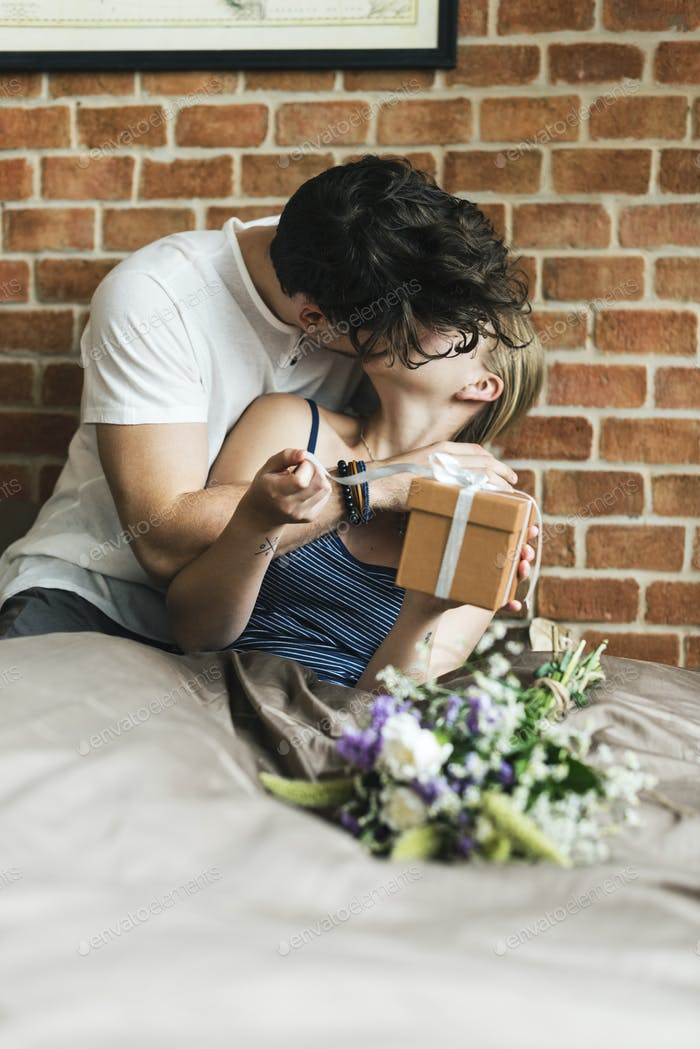 Wife receives a gift box and a bouquet of flower from husband