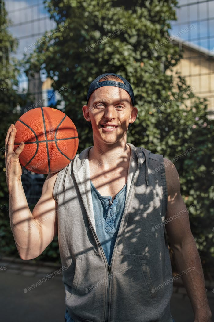 Handsome young basketball player with a ball