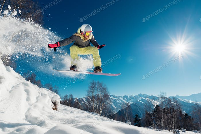 Girl is jumping with snowboard