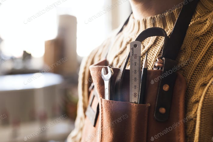 Midsection of carpenter with work tools in apron pocket at workshop