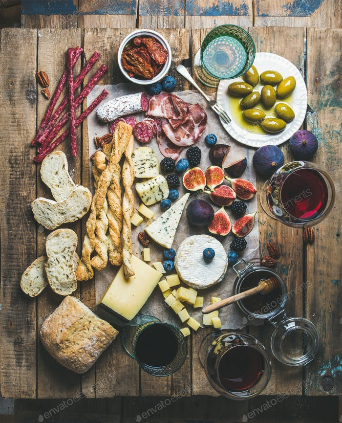 Wine and snack set with wines, meat, bread, olives, berries