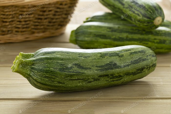 Fresh green spotted courgette on a cuttingboard close up