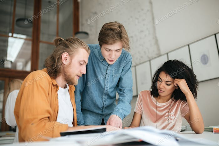 Two boys with blond hair and girl with dark curly hair working together on new project in classroom
