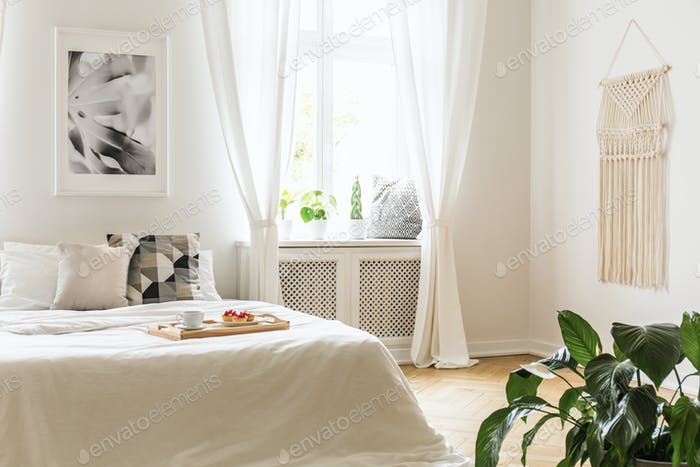 Breakfast tray with pastries and coffee on a cozy, white bed in