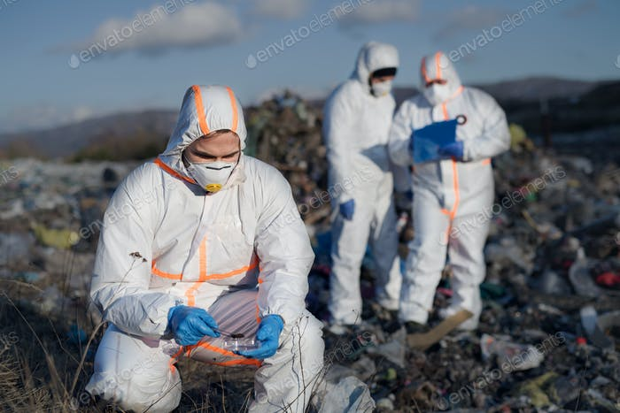 Group of activists with protective masks on landfill, environmental pollution concept