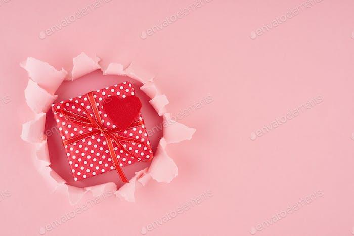 Valentinstag. Ein gerissenes Loch und rotes Herz mit Geschenkbox in leuchtendem Rosa