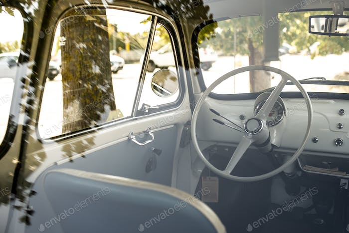 Interior of small white vintage car on the street. No people. Wh