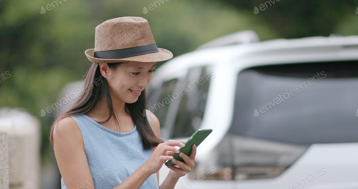 Travel woman checking the destination on cellphone during the road trip