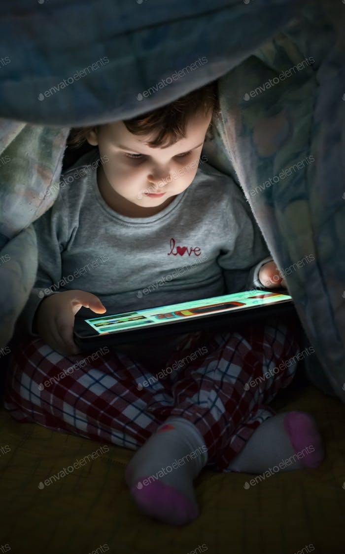 Little girl watching her tablet in the bed. Illuminated child fa