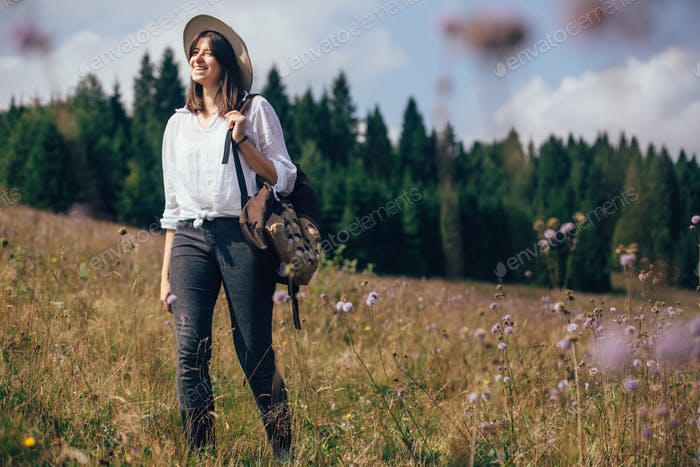 Hipster Mädchen mit Rucksack Reisen in Wildblumenwiese