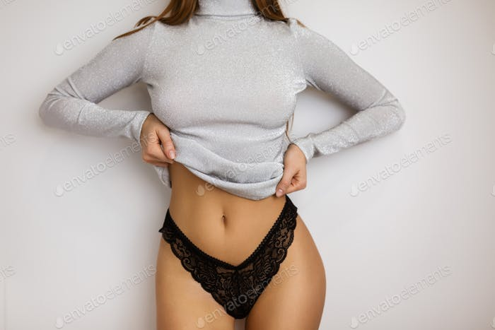 Slim woman body standing in black lingerie and gray turtleneck on gray background