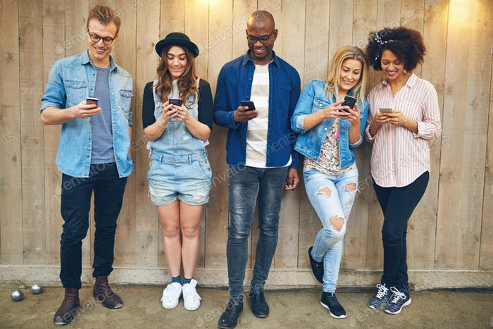 Cheerful multiracial friends messaging with smartphones at wooden wall