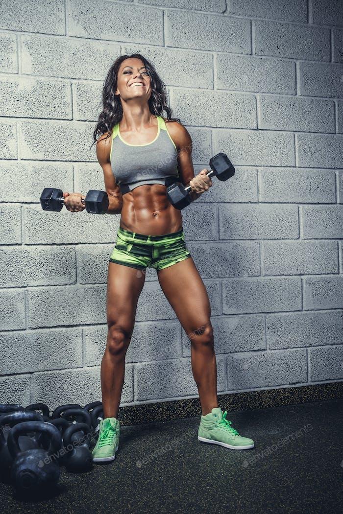 Sporty suntanned female posing with dumbbells.