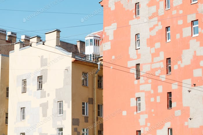 Old houses of European city. Walls of pastel colors with restoration.