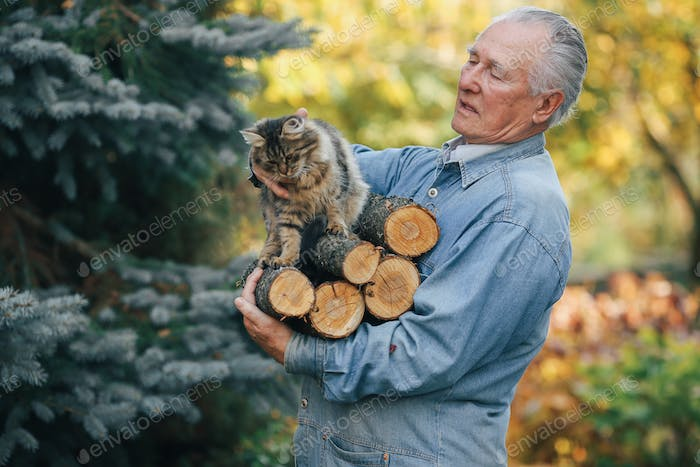 Adult man holding a firewood in his hand