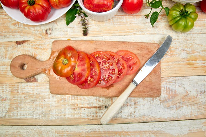 Chopped tomatoes and knife on cutting board.