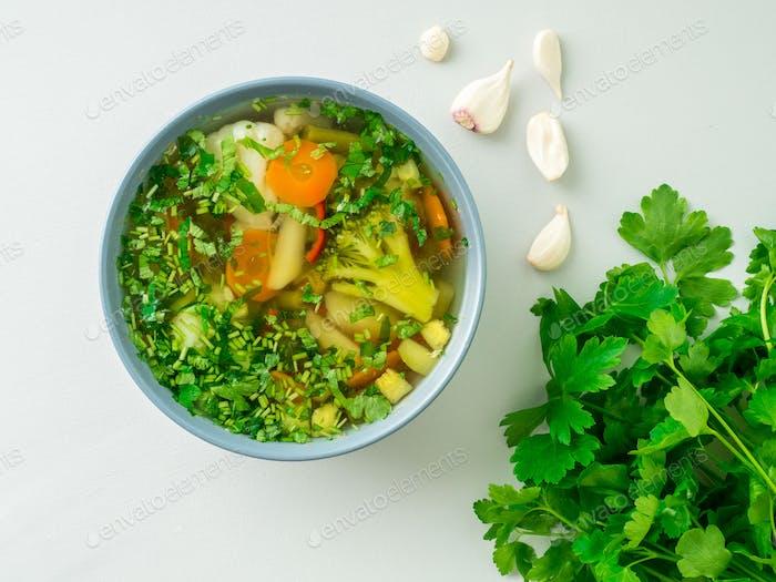 Gesunde Frühlingsgemüse vegetarische Suppe, grauer Betonhintergrund, Draufsicht, Nahaufnahme.